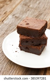 Homemade brownies sliced on white plate over wooden table.