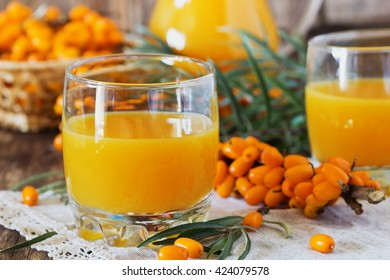Homemade buckthorn soft drink in a glass and ripe sea buckthorn berries on the table.  Healthy and diet food. Selective focus