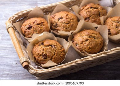 Homemade buckwheat muffins with dried fruits in a basket on a wooden table, selective focus