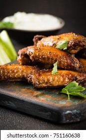 Homemade Buffalo chicken wings with blue cheese dip and celery sticks on dark background