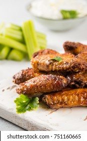 Homemade Buffalo chicken wings close up with blue cheese dip and celery sticks on light background