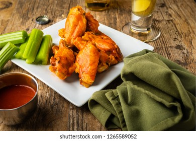 Homemade Buffalo style chicken wings on a plate with celery and a cold beer.   A side bowl of wing sauce for dipping is present with green napkin