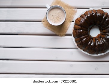 Homemade Bundt cake with chocolate icing, cup of hot coffee on a white wooden table. Top view.
