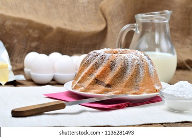 Homemade bundt cake sprinkled with sugar, milk and eggs in background