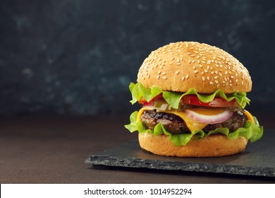 Homemade burger with beef cutlet, cheddar, lettuce and vegetables on slate board with copy space. Concept unhealthy food.