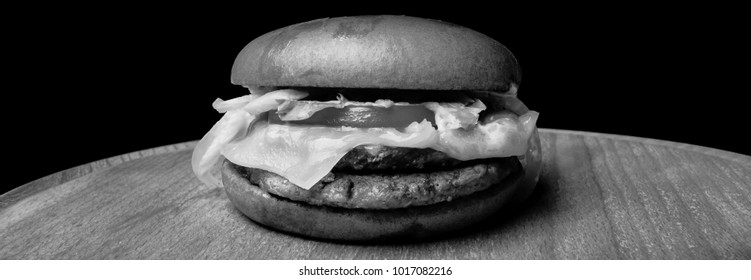 Homemade burger with beef on wooden background. Fresh tasty hamburger with pork, cheese, tomato, onion and lettuce and french fries on a wooden table and dark background. Black and white photo