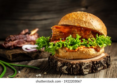 Homemade burger with grilled ribs, vegetables, sauce on rustic wooden background. fast food and junk food concept.