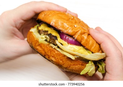 Homemade burger in hands on light background.