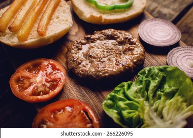 Homemade burger ingredients arranged on vintage wooden plate