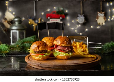 Homemade burgers and fries on wooden board with Christmas decor on the wall, closeup view