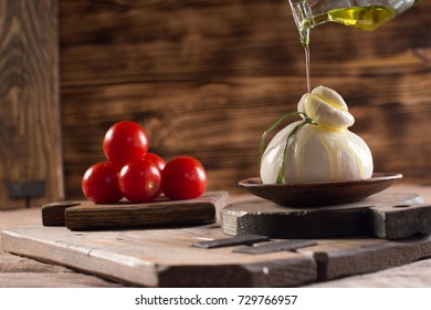 Homemade burrata cheese with olive oil and tomatoes