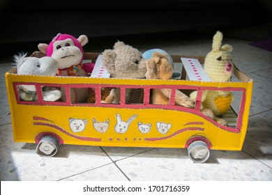 Homemade bus for kids, made of cardboard, painted yellow, with dolls as passengers.