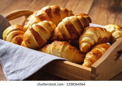 Homemade butter croissants on wooden tray.