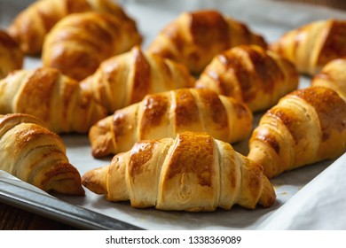 Homemade butter croissants on wooden background.