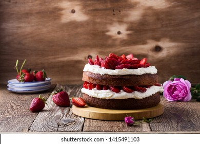 Homemade buttercream cake with strawberries, festive table with pink roses and berries, rustic wooden background