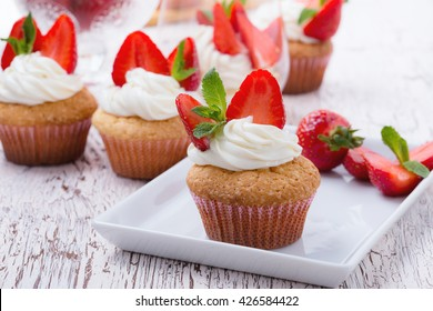 Homemade buttercream cupcakes with strawberries and fresh mint on white wooden table