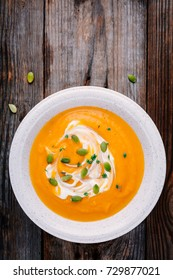 Homemade butternut squash soup with cream and seeds on wooden background