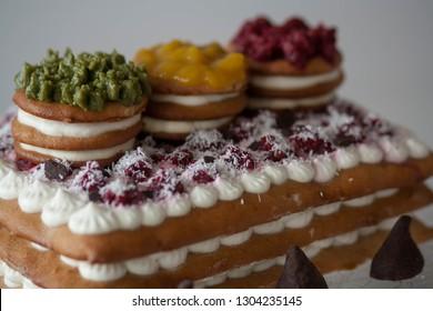 homemade cake, 3 layers with cream and raspberry on the top. Traffic light cake. Red (raspberry), Orange (mango), Green (matcha tea). Cream cheese and truffle.