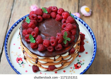 Homemade cake with cream, raspberry and chocolate, selective focus. Rustic style