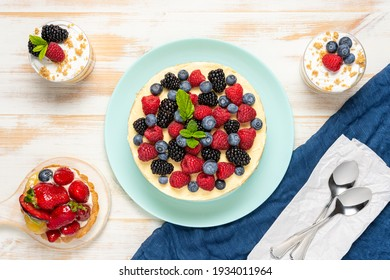 Homemade cake with fresh berries on wooden background.