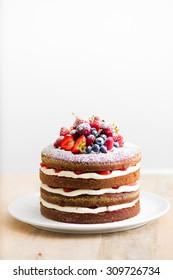 Homemade cake with fresh berries on the top before white background. Empty space for text.
