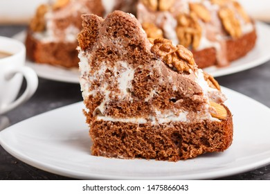 Homemade cake with milk cream, cocoa, almond, hazelnut on a black concrete  background and a cup of coffee. Side view, close up, selective focus.