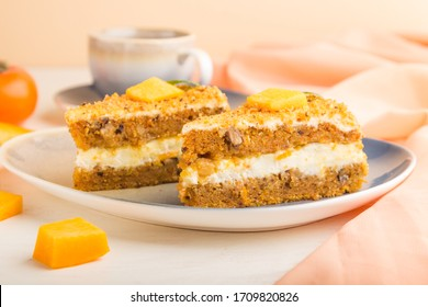 Homemade cake with persimmon and pumpkin and a cup of coffee on a white wooden background with orange textile. side view, close up, selective focus.