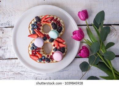 Homemade cake in shape of number 8 decorated with white cream and berries and flowers tulips. Sweet dessert as a gift for women's day on the eighth of March