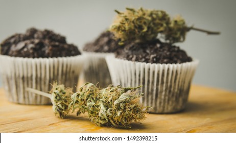 Homemade cakes with cannabis and buds of marijuana. Concept of using marijuana in food industry. Cake with CBD cannabis and buds of marijuana on the grey background