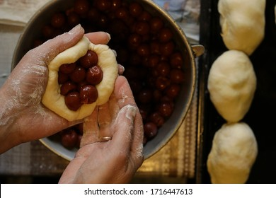 homemade cakes with cherries. homemade vipette. easter cake. cooking homemade bun. hand sculpting with dough. roll with cherries at home. pie in female hands on a dark background