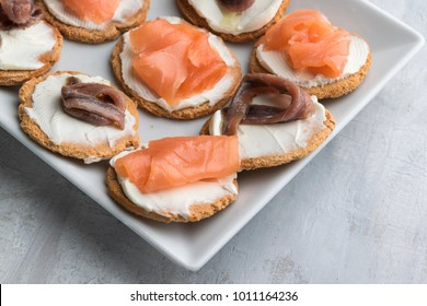 Homemade canapes with smoked salmon, anchovies and cream cheese. Lifht gray background. Copy space.