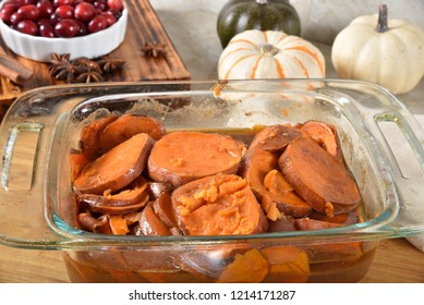 Homemade candied yams in a baking dish cooling on a cutting board`