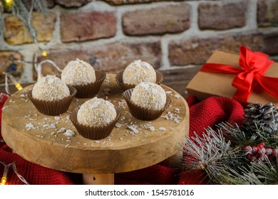 Homemade candies with coconut roasted almonds on a Christmas season table decorated with lights.