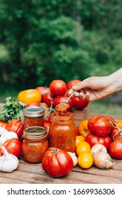 Homemade canned tomato sauce  in glass jars for winter on wooden table with basil, garlics, herbs and fresh tomatoes, women hand holding spoon with souce