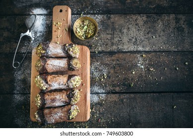 Homemade cannoli with pistachios servd on wooden board with blank space