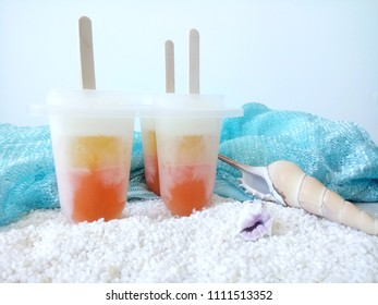 Home-made cantaloupe popsicle on the white sand.