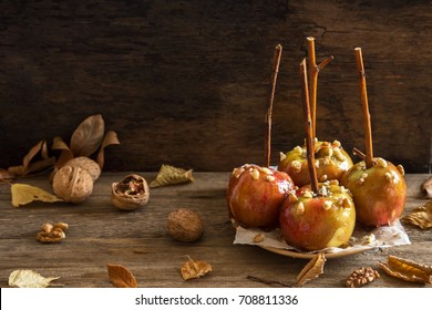 Homemade Caramel Apples on a Stick for Halloween. Organic Snack - Caramel Apples with Walnuts.