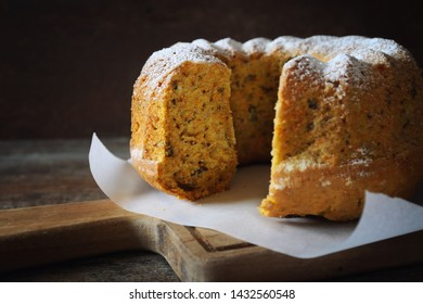 Homemade carrot bundt cake with walnuts on wooden  background