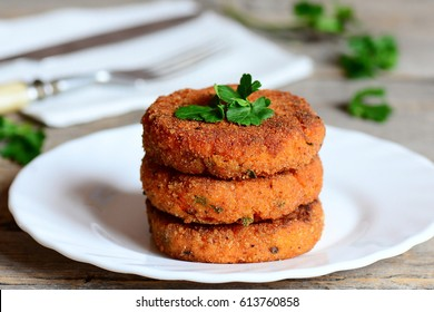 Homemade carrot burgers on a plate. Delicious carrot burgers with green onions and parsley. Closeup