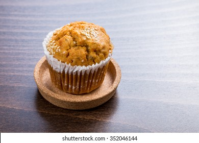 Homemade carrot muffin with empty space on brown wooden background