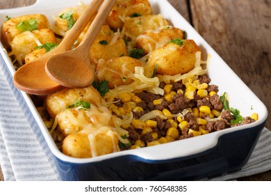 Homemade casserole of Tater Tots with minced beef, corn and cheese close-up in a baking dish on a table. horizontal