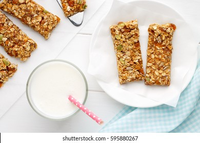 Homemade cereal snacks for healthy eating. Granola bars with milk on white wooden background. Top view.