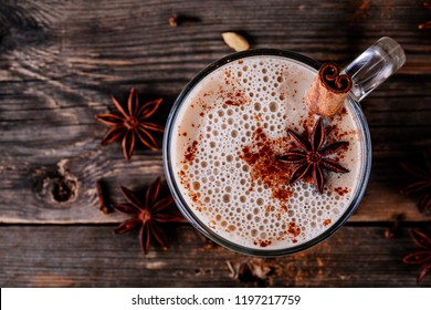 Homemade Chai Tea Latte with anise and cinnamon stick in glass mug on wooden rustic background. Top view