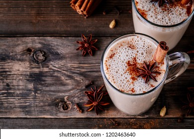 Homemade Chai Tea Latte with anise and cinnamon stick in glass mugs on wooden rustic background