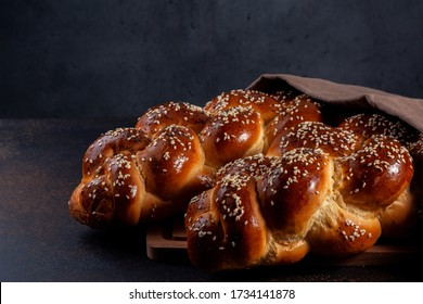 Homemade Challah -  special bread in Jewish cuisine.Main ingredients are eggs, white flour, water, sugar, salt  and yeast. Decorated  with sesame and poppy seeds. Dark background.