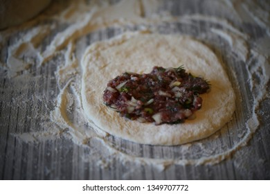 Homemade chebureks are cooked on the table with flour
