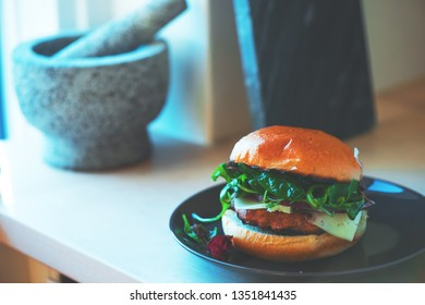 Homemade cheese burger on a plate next to mortar and pestle set