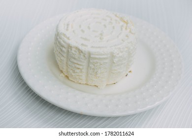 homemade cheese on a white plate on a white background.Adyghe cheese from milk. Home cheese making