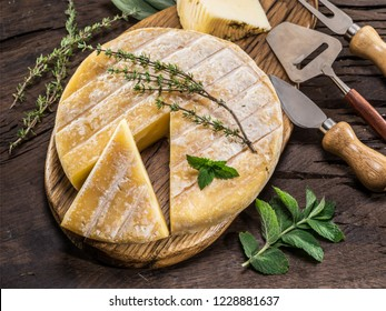 Homemade cheese wheel on the dark wooden background. Top view.