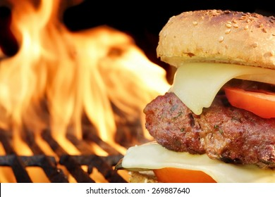 Homemade Cheeseburger Close-up On Flaming Barbecue Grill Background. Snack For Picnic or Outdoor Party.